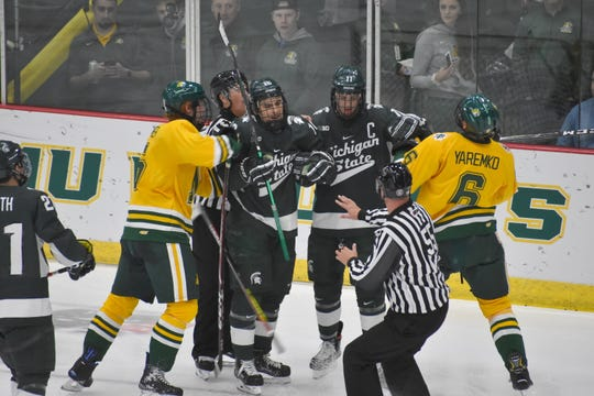 Northern Michigan's Mason Palmer (left), Michigan State's Brody Stevens (16) and Tommy Apap (11) and NMU's Rylan Yaremko fight near the Wildcats net during the second period Saturday in Marquette.