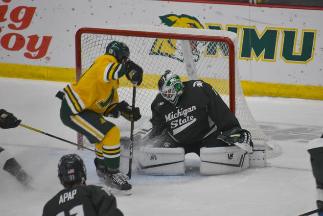 Northern Michigan's Joe Nardi tries to tuck the puck past Michigan State goalie Drew DeRidder during the first period Saturday in Marquette,