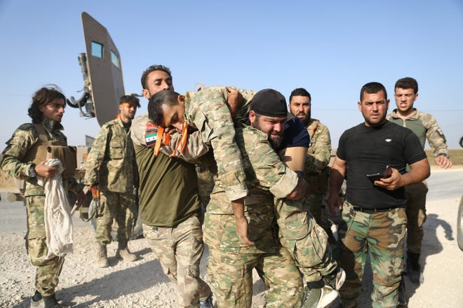 Turkish-backed Syrian fighters evacuate a wounded comrade near the border town of Ras al-Ain on Sunday, Oct. 13, 2019, as Turkey and its allies continued their assault on Kurdish-held border towns in northeastern Syria. Turkish forces and their proxies pushed deep into Syria Sunday, moving closer to completing their assault's initial phase, while Washington announced it was pulling out 1,000 troops from the country's north.