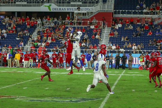 An FAU defender knocks the ball away from MTSU's Jimmy Marshall (83) during Saturday's game.