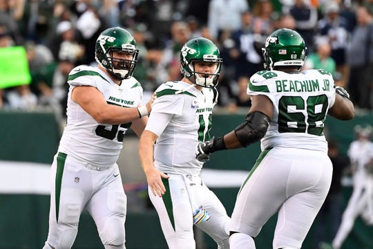 New York Jets center Ryan Kalil (far left), quarterback Sam Darnold (center), and offensive tackle Kelvin Beachum (68) celebrate Darnold's 92-yard touchdown pass to Robby Anderson (not pictured) in the second quarter. The New York Jets face the Dallas Cowboys in NFL Week 6 on Sunday, Oct. 13, 2019, in East Rutherford.