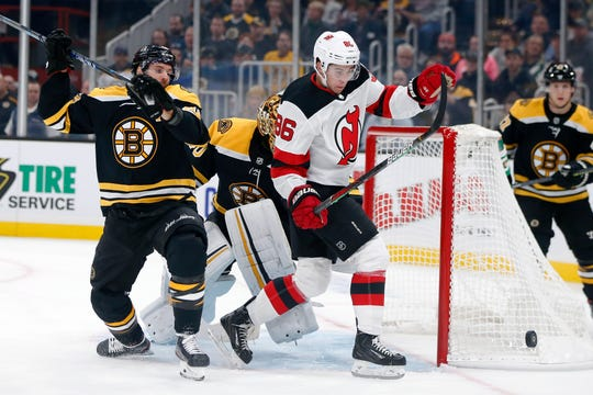 Boston Bruins' David Krejci, left, defends against New Jersey Devils' Jack Hughes (86) during the first period of an NHL hockey game in Boston, Saturday, Oct. 12, 2019.