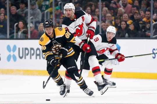 New Jersey Devils' Travis Zajac (19) and Boston Bruins' David Pastrnak (88) battle for the puck during the first period of an NHL hockey game in Boston, Saturday, Oct. 12, 2019.