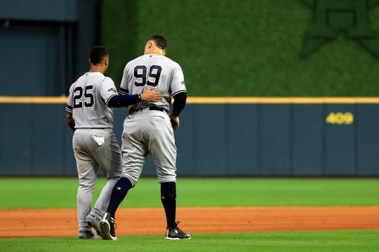 Gleyber Torres #25 and Aaron Judge #99 of the New York Yankees head to their positions after batting in the seventh inning against the Houston Astros in game one of the American League Championship Series at Minute Maid Park on October 12, 2019 in Houston, Texas.