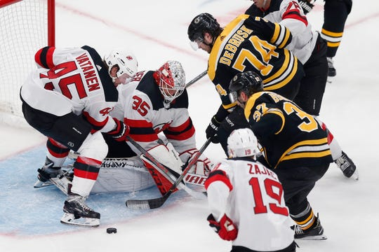 New Jersey Devils' Cory Schneider (35) and Sami Vatanen (45) struggle to gain control of the puck as Boston Bruins' Patrice Bergeron (37) comes in to score during the second period of an NHL hockey game in Boston, Saturday, Oct. 12, 2019.