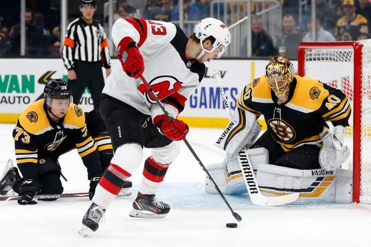 New Jersey Devils' Nico Hischier (13) tries to shoot against Boston Bruins goalie Tuukka Rask (40) during the first period of an NHL hockey game in Boston, Saturday, Oct. 12, 2019.