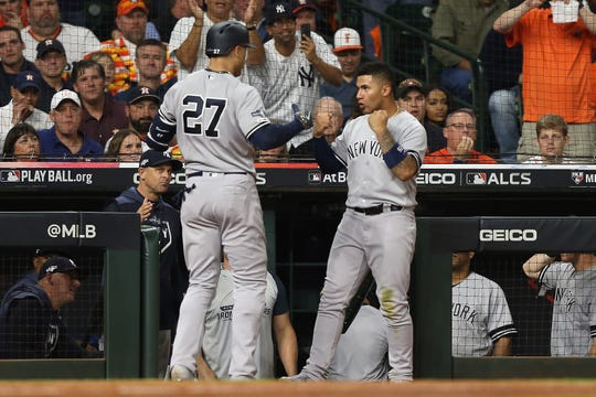 Giancarlo Stanton #27 of the New York Yankees is congratulated by his teammate Gleyber Torres #25 after his solo home run against the Houston Astros during the sixth inning in game one of the American League Championship Series at Minute Maid Park on October 12, 2019 in Houston, Texas.