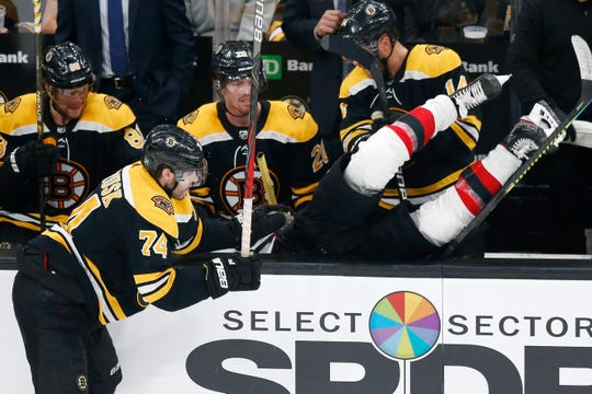 Boston Bruins' Jake DeBrusk (74) checks New Jersey Devils' Kevin Rooney into the Bruins' bench during the third period of an NHL hockey game in Boston, Saturday, Oct. 12, 2019.
