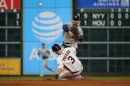 Oct 12, 2019; Houston, TX, USA; New York Yankees second baseman Gleyber Torres (25) turns a double play against Houston Astros right fielder Kyle Tucker (3) in the third inning in game one of the 2019 ALCS playoff baseball series at Minute Maid Park.