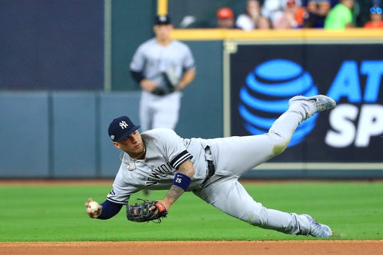 Gleyber Torres #25 of the New York Yankees throws out the runner after making a diving stop against the Houston Astros during the first inning in game one of the American League Championship Series at Minute Maid Park on October 12, 2019 in Houston, Texas.