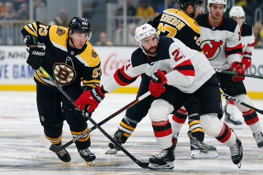 Boston Bruins' Brad Marchand (63) defends against New Jersey Devils' Kyle Palmieri (21) during the first period of an NHL hockey game in Boston, Saturday, Oct. 12, 2019.