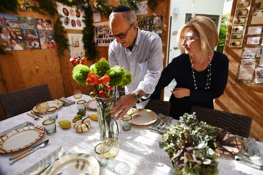 Nina Kampler and her husband Zvi Marans arrange flowers on the table inside the Sukkah at their home in Teaneck, photographed on 10/13/19.