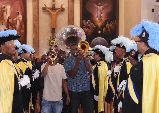 The Soul Express Brass Band leads the faithful in  a second line dance out of Holy Ghost Catholic Church Sunday. The occasion was the completion of Holy Mass celebrating the 100th anniversary of the largest African-American Catholic church in the United States.