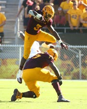 Arizona State Sun Devils running back Eno Benjamin (3) jumps over the Washington State Cougars defender in the second half during a game on Oct. 12, 2019 in Tempe, Ariz.
