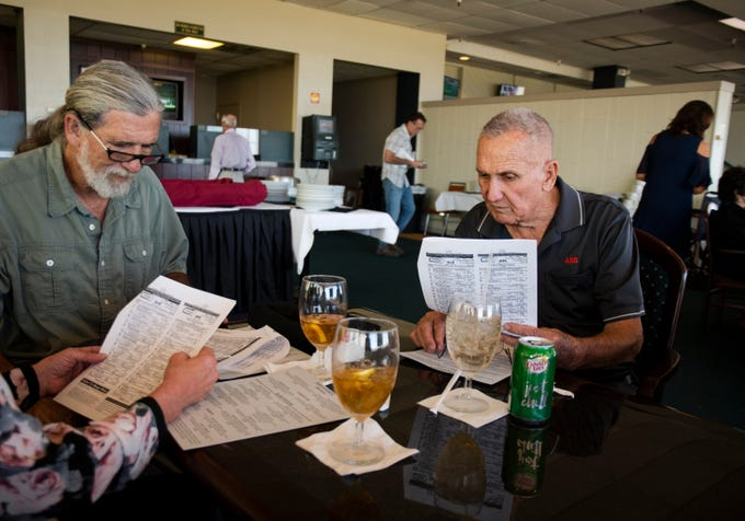 91-year-old Bill Shaner, right, and his son Richard Shaner read the racetrack program on opening day at Turf Paradise, Saturday, Oct. 12, 2019.