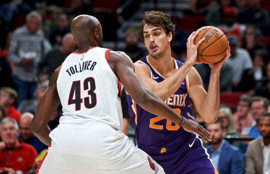 Phoenix Suns forward Dario Saric, right, drives toward Portland Trail Blazers forward Anthony Tolliver during the second half of a preseason NBA basketball game in Portland, Ore., Saturday, Oct. 12, 2019. (AP Photo/Craig Mitchelldyer)