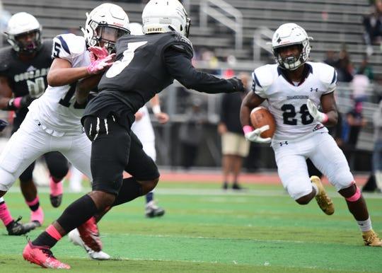 Chambersburg's Sam Vessah (15)  attempts to stop Harrisburg's Nateur Dennis (3) to allow the Trojans' Keyshawn Jones (28) to run the ball on Saturday, Oct. 12, 2019.
