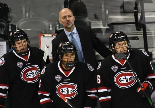 Huskies' head coach Brett Larson and his players look on as St. Cloud State battled with Bemidji State on Saturday evening.