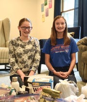 """Kennedy Community School eighth-graders Keara Moore and Erin Wald gather donations Sunday, Oct. 13, 2019 for """"parent essential bags,"""" which will be given to parents of children with cancer at Minneapolis Children's Hospital."""