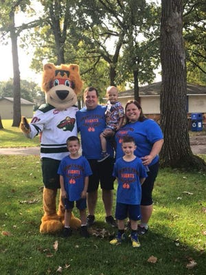Elk River residents Derek and Jessica Blonigen stand meet the Minnesota Wild mascot with their three sons, 6-year-old Grant, 8-year-old Spencer and 10-year-old Caleb.