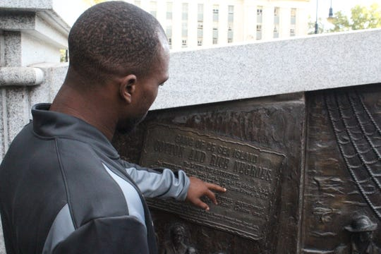 FAMU running back Bishop Bonnett reads an inscription on a monument outside the South Carolina Statehouse in Columbia on Friday, Oct. 11, 2019.