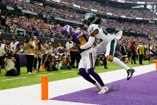 Minnesota Vikings wide receiver Adam Thielen catches a touchdown pass in front of Philadelphia Eagles cornerback Sidney Jones, right, during the first half of an NFL football game, Sunday, Oct. 13, 2019, in Minneapolis.