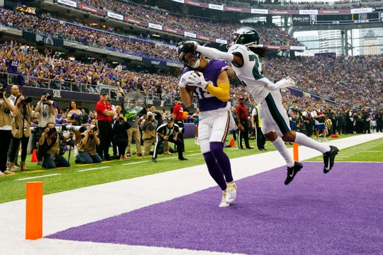 Minnesota Vikings wide receiver Adam Thielen catches a touchdown pass in front of Philadelphia Eagles cornerback Sidney Jones, right, Sunday, Oct. 13, 2019, in Minneapolis.