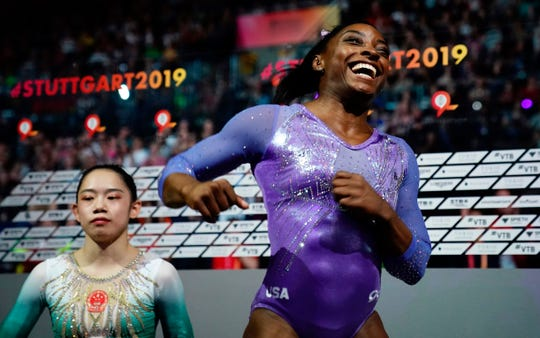 Simone Biles celebrates after winning the beam apparatus final as second placed China's Liu Tingting looks on at the Gymnastics World Championships.