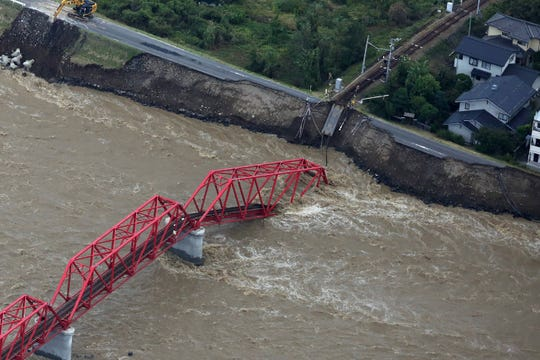 This aerial view shows a damaged train bridge over the swollen Chikuma river in the aftermath of Typhoon Hagibis in Ueda, Nagano prefecture on October 13, 2019.