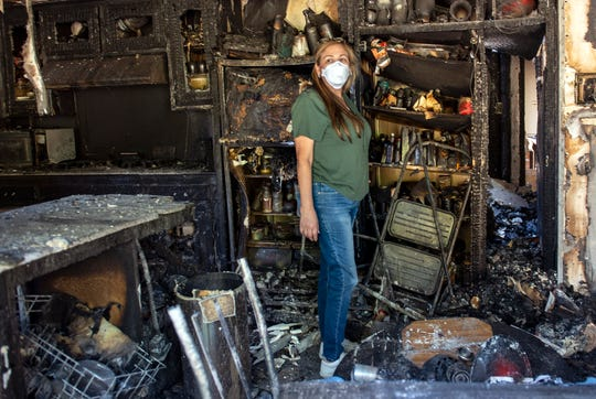 Loretta Reel surveys the damage to her in-laws' home in the Porter Ranch area of Los Angeles on Oct. 12, 2019.