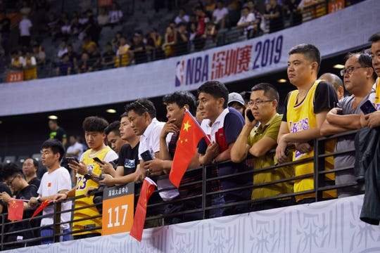 Fans hold Chinese flags as they watch the NBA preseason game between the Lakers and Nets in China.