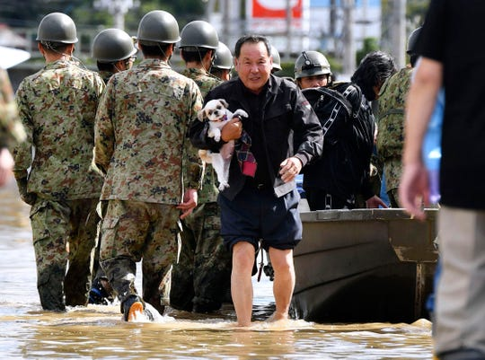 An evacuee with a dog is rescued by Self-Defense force members as the city is hit by Typhoon Hagibis, in Motomiya, Fukushima prefecture, northern Japan, Sunday, Oct. 13, 2019.