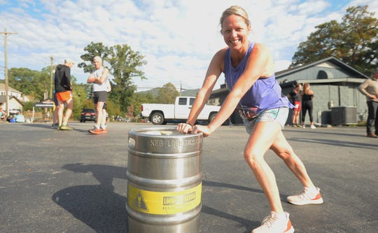Lessye Ashworth stretches with the help of a keg before the start of the 2019 Lookout to Lookout to Lookout 10-mile Race. Ashworth, who was participating in the trail run for the first time, was one of more than 180 people, on Oct. 12, to run from Lookout Brewing Co. to the top of Lookout Mountain and back.