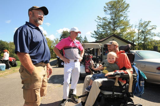 Britten Olinger, his son Easton, Eddie Collie, middle, and Kevin Kruta talk before the Britten Strong Golf Tournament at Black Mountain Golf Course on Oct. 11.