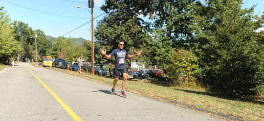 A trail runner celebrates on the final stretch of the Oct. 12 Lookout to Lookout to Lookout 10-mile Race in Black Mountain.
