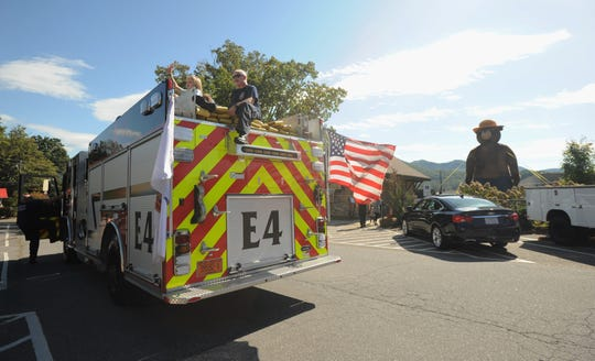 A Black Mountain firefighter escorts a young visitor to top of a fire truck, Oct. 12, as the Black Mountain Fire Department celebrated 100 years of service with a festival and parade.