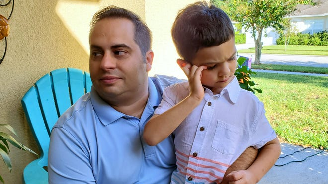 "Jonathan Pogar sits with his 7-year-old son, Andrew. Andrew exhibits ""autism-like"" symptoms and was recently denied access to his behavioral therapist in the classroom."