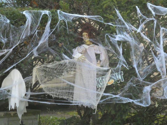 A macabre figure hides in the landscaping of a home at 902 Rogers Street.