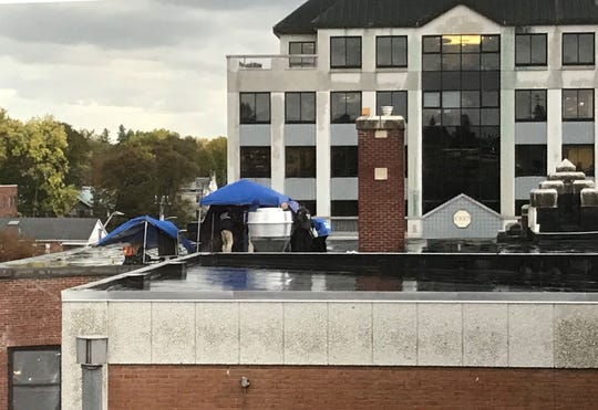 Burlington Police detectives investigate a body found on the roof of Mr. Mike's restaurant in Burlington on Monday afternoon, Oct. 14, 2019.