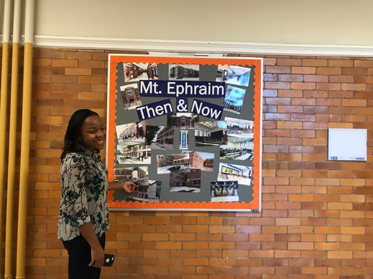 Giana Solomon of Uncommon Schools shows a collage depicting the history of Bonsall Elementary School, which opened on Mount Ephraim Avenue in Camden in 1914.