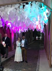 Kaitlan Hyland and David Wovrosh pose for a photo after exchanging wedding vows under a Blink light installation of paper leaves made by artist Jessica Wolf on Friday, Oct. 11, 2019, in Sellew Alley next to Findlay Market.