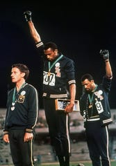 "U.S. athletes Tommie Smith, center, and John Carlos give ""black power"" salutes during medal ceremony at the the Summer Olympic Games in Mexico City on Oct. 16, 1968."