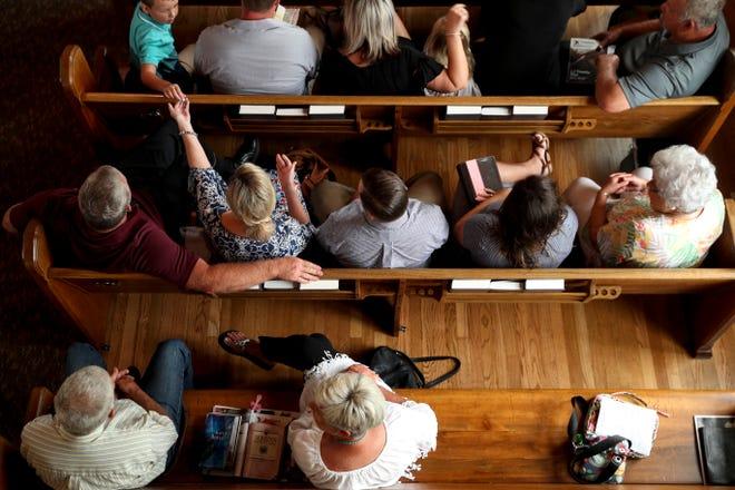 Churchgoers make small talk before a service at Orlinda Baptist Church.