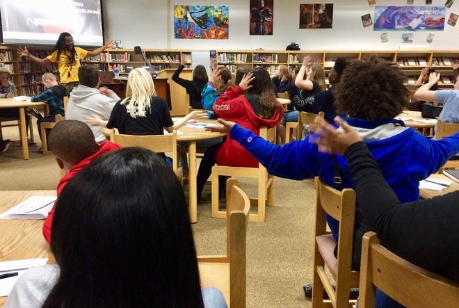 Kennedy Center teaching artist, Bomani Armah, leads about 60 Kenwood Middle School students in a hip-hop writing class. Grabbing the sides of your head and blasting your hands out symbolizes prewriting in Armah's hip-hop dance.