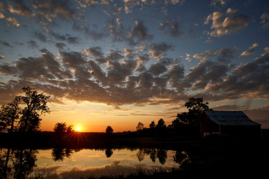 The sun sets over a small pond that separates the Lackeys' house from farmland in Orlinda, Tenn.