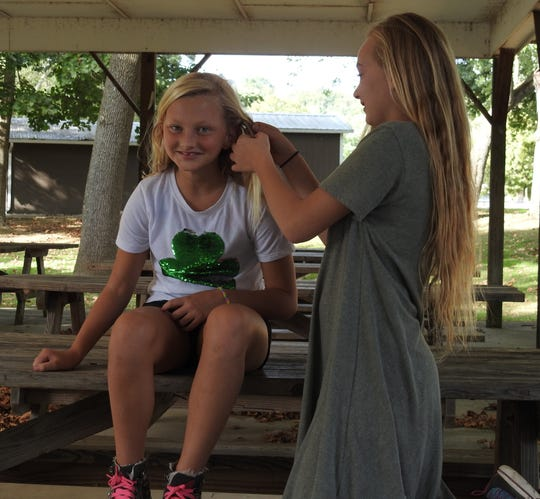 Katie Walser has her hair braided by Rebekah Roe. Both are in sixth grade at Warsaw Elementary School, as are Rebekah's brothers and sister.