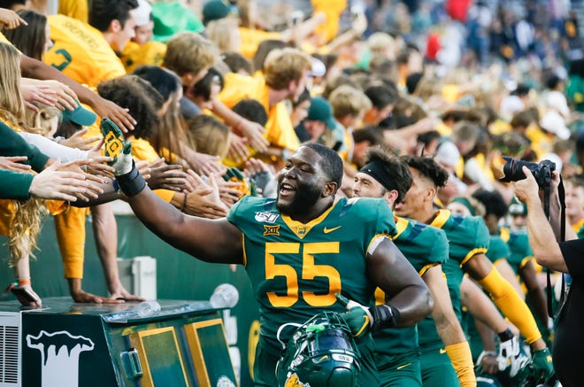 Baylor players exchange high-fives with fans following a double-overtime win over Texas Tech on Saturday.