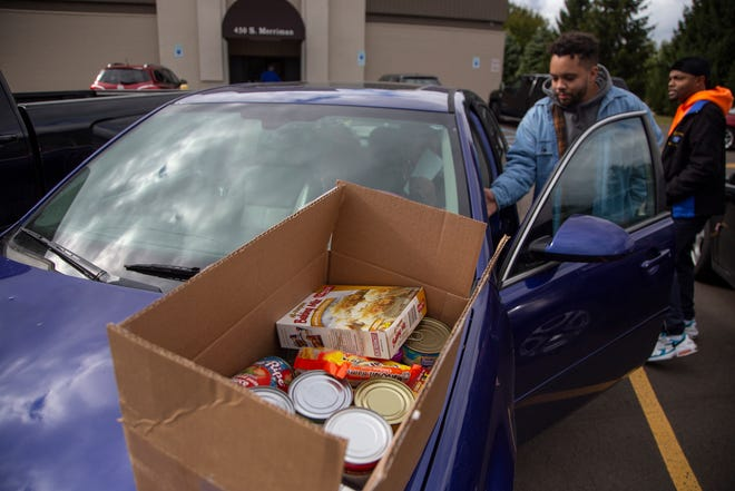 Kevin Donnellon, 23, of Eastpointe a striking GM worker checks out a box of supplies that include canned goods and ramen at the Local 163 in Westland, Monday, Oct. 14, 2019. Ford and FCA workers are donating food and other items to help strikers make ends meet.
