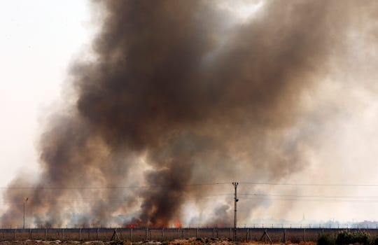 In this photo taken from the Turkish side of the border between Turkey and Syria, in Akcakale, Sanliurfa province, southeastern Turkey, smoke billows from fires on targets in Tel Abyad, Syria, caused by bombardment by Turkish forces, Sunday, Oct. 13, 2019. The United Nations says at least 130,000 people have been displaced by the fighting in northeastern Syria with many more likely on the move.