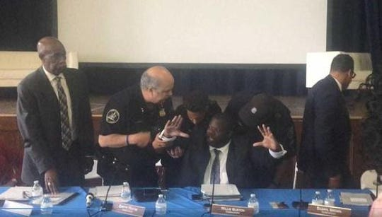 Police officers remove police commissioner Willie Burton from a board meeting where facial recognition software was discussed.